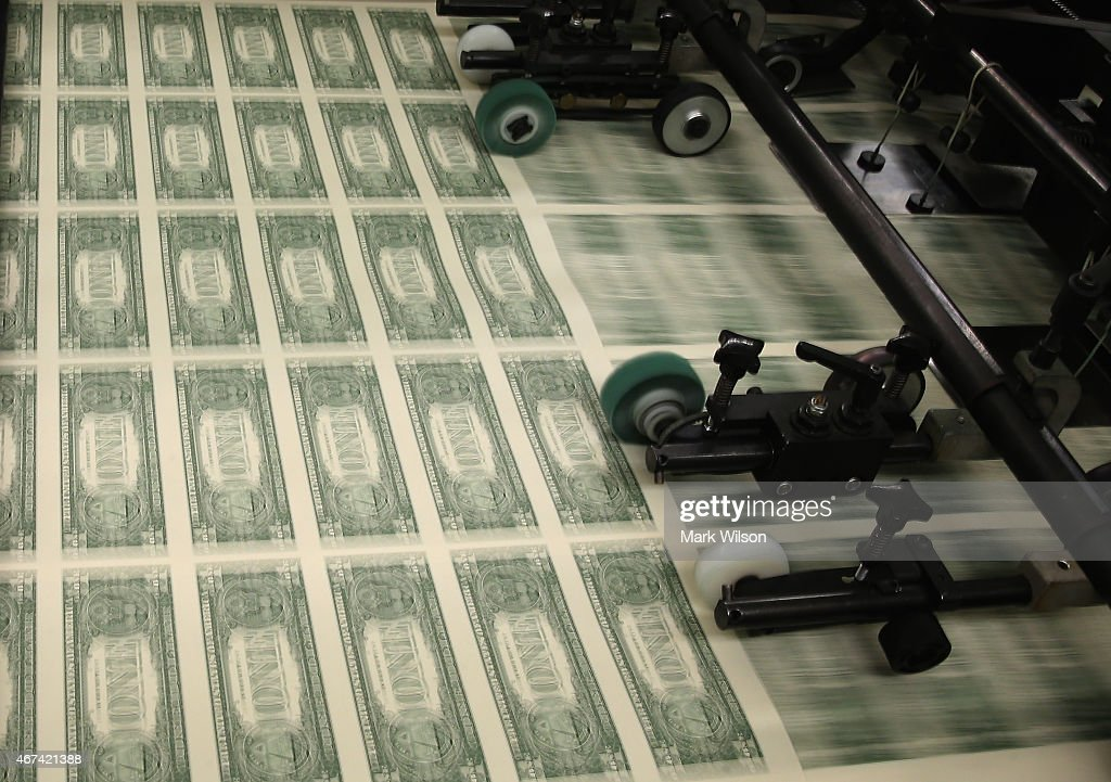 Sheets of one dollar bills run through the printing press at the Bureau of Engraving and Printing on March 24 2015 in Washington DC The roots of The...