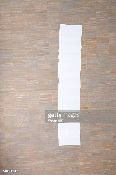 Sheets of paper in shape of exclamation mark on floor