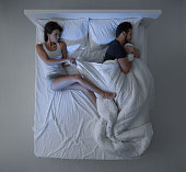 Couple sleeping in bed, the man is stealing the duvet and the woman is angry and freezing