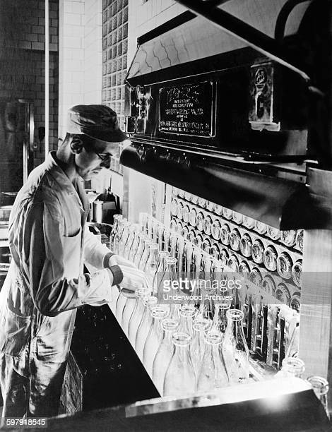 A Sheffield Dairy Farms worker inspecting milk bottles during the sterilization process at their New York City plant New York New York circa 1926