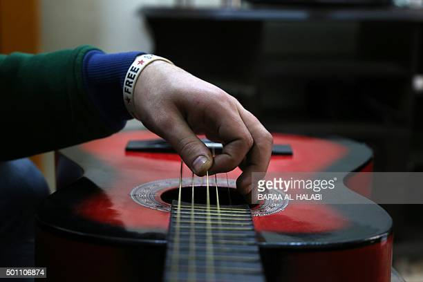 Shehab a 23yearold Syrian tunes his guitar inside his home in the northern Syrian city of Aleppo on December 12 2015 Shehab a freelance videographer...