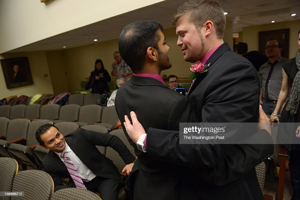 Shehan Welihindha, center, embraces Ryan Wilson, right, before they were one of seven same-sex couples to become some of the first to be married in the state of Maryland at Baltimore City Hall on Tuesday January 01, 2013 in Baltimore, MD. Baltimore Mayor Stephanie Rawlings-Blake officiated the first of the seven marriages.