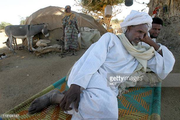 Sheikh Abdarahman Musa rests on a bed with fellow Arab nomadic tribespeople at their home in the Aramba area of North Darfur The nomads have occupied...