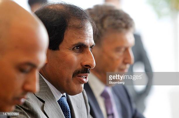 Sheikh Abdullah Saud Al Thani governor of Qatar's central bank center speaks as Ali Shareef Al Emadi group chief executive officer of Qatar National...