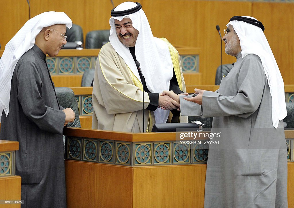 Sheikh Ahmad Humud al-Jaber al-Sabah First Deputy Prime Minister and Minister of Interior speaks to Kuwaiti MP's Adnan AbdulSamad (R) and Nabil al-Fadhel during a parliament session at Kuwait National Assembly in Kuwait City on January 8,2013. Kuwait parliament overwhelmingly approved the controversial electoral decree that caused the opposition in the oil-rich Gulf state to boycott the December 1 general elections.