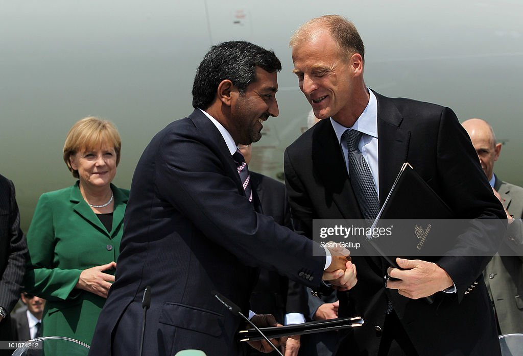 Sheikh Ahmed bin Saeed Al Maktoum (C), Chairman of Emirates airline, and Thomas Enders, CEO of European aircraft manufacturer Airbus, shake hands after signing an agreement confirming that Emirates is to purchase more Airbus A380 aircraft as German Chancellor Angela Merkel (L) looks on at the ILA Berlin Air Show on June 8, 2010 in Berlin, Germany. Emirates will buy an additional 32 A380 aircraft, bringing its total A380 fleet to 90 aircraft.