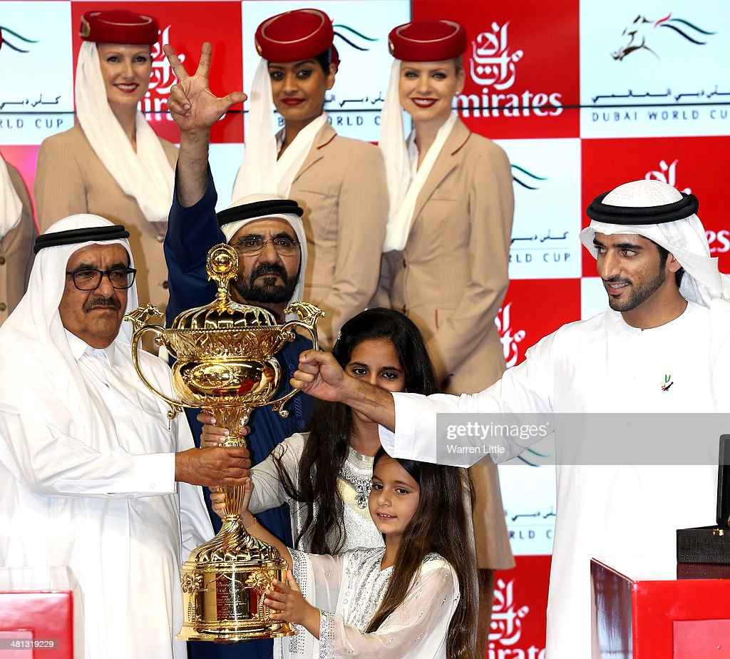 Sheikh Hamdan Bin Rashid Al Maktoum, Sheikh Mohammed bin Rashid Al Maktoum, Ruler of Dubai and Vice President of the UAE and Sheikh Hamdan bin Mohammed bin Rashid Al Maktoum, Crown Prince of Dubai pose with the trophy afterwinning the Dubai World Cup with his horse African Story ridden by Silvestre De Sousa at the Meydan Racecourse on March 29, 2014 in Dubai, United Arab Emirates.