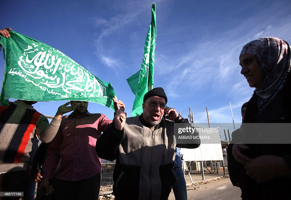 Sheikh Hassan Yousef (C), a prominent leader of the Hamas Islamic movement, holds the party's flag and talks on a phone following his release on January 19, 2014 after spending 28 months in Israel's Ofer prison, near the West Bank city of Ramallah. Yousef, who is also a member of the Ramallah-based Palestinian Legislative Council, told reporters after being released that he would work with Hamas rivals 'Fatah and other Palestinian factions to achieve reconciliation.'