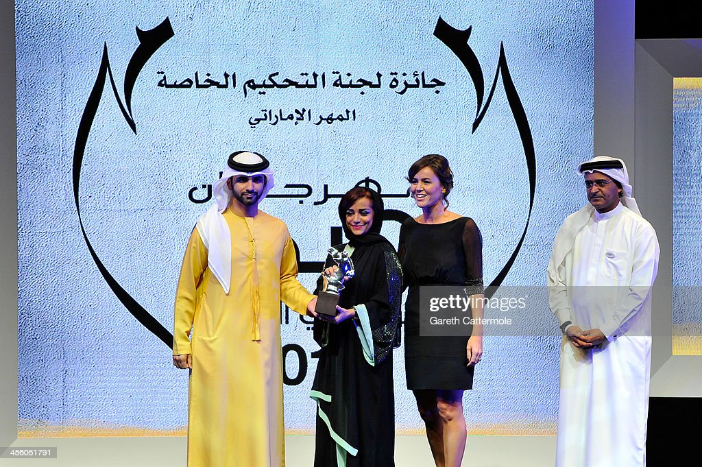 Sheikh Mansoor bin Mohammed bin Rashid Al Maktoum presents director Nayla Al Khaja and producer Claudia Corbelli with their Muhr Emirati Special Jury Prize award with DIFF Chairman Abdulhamid Juma (R) at the Muhr Awards on stage during day eight of the 10th Annual Dubai International Film Festival held at the Madinat Jumeriah Complex on December 13, 2013 in Dubai, United Arab Emirates.