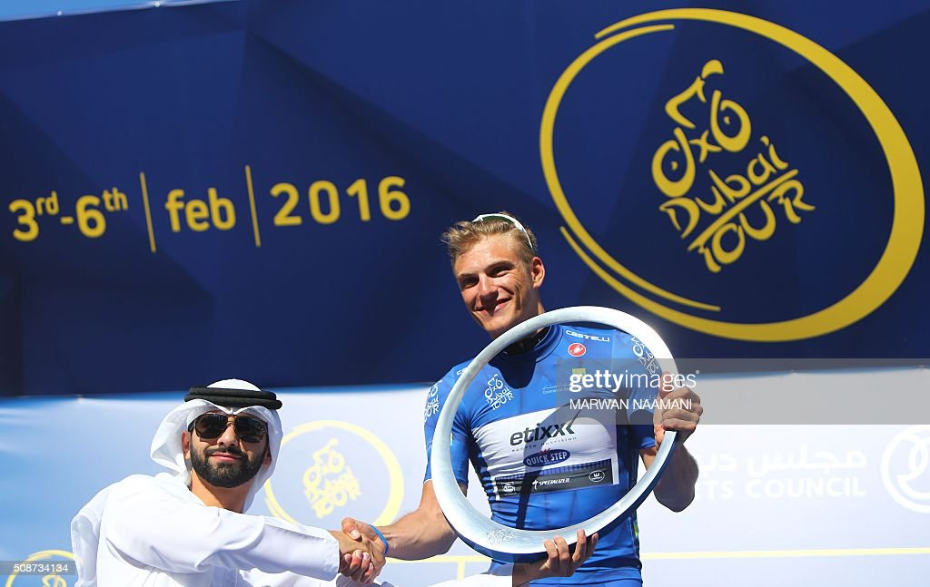 Sheikh Mansour (L), the son of the ruler of Dubai awards German cyclist Marcel Kittel of the Etixx-Quick Step team the third edition of the Dubai Tour 2016 trophy after he won the fourth and last stage of the cycling competition on February 6, 2016 in Dubai. / AFP / MARWAN NAAMANI