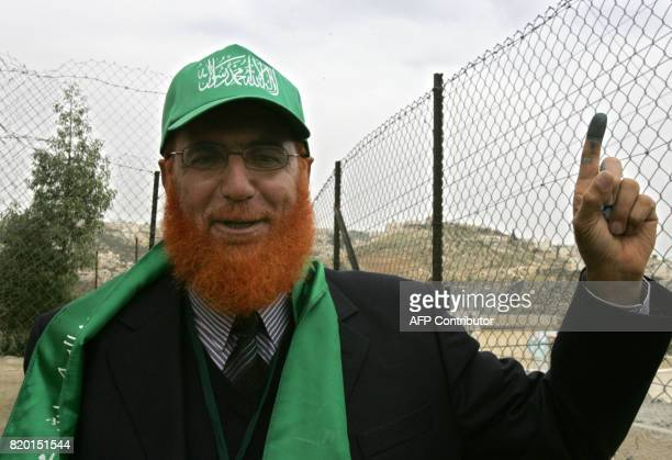 Sheikh Mohammed Abu Tir a Hamas candidate and a Palestinian resident of Arab East Jerusalem wears the party colours as he shows off his inkstained...