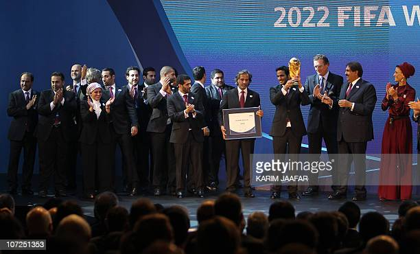 Sheikh Mohammed bin Hamad alThani chairman of the Qatar 2022 bid committee raises the World Cup trophy as he stands with Qatar's Emir Sheikh Hamad...