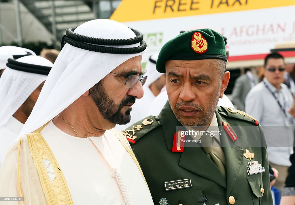 Sheikh Mohammed bin Rashid Al Maktoum, the ruler of Dubai, left, with Major General Atiq Juma Ali bin Darwish, director of defense for the UAE, tours aircraft on display during the 13th Dubai Airshow at Dubai World Central (DWC) in Dubai, United Arab Emirates, on Sunday, Nov. 17, 2013. The 13th edition of the biennial 2013 Dubai Airshow, the Middle East's leading aerospace event organized by F&E Aerospace. Photographer: Duncan Chard/Bloomberg via Getty Images
