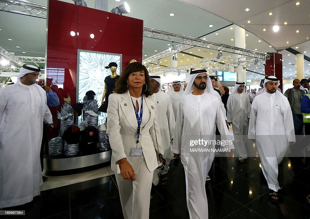 Sheikh Mohammed Bin Rashid al-Maktoum (C), governer of Dubai, tours the newly opened Al-Maktoum International airport, the emirate's second airport in Dubai, on October 27, 2013. The new passenger terminal opened its doors for business following an official inauguration and welcome of the first commercial flight. Lady to the left is an official.