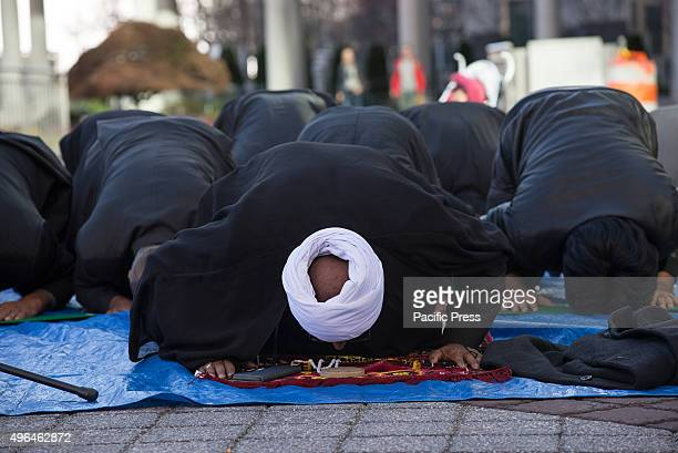 Sheikh Sakhawat Hussain prostrates himself as he leads participants in prayer before the start of the procession Shia Muslims gathered in Jersey City...