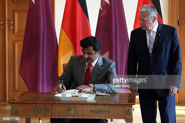 Sheikh Tamim bin Hamad Al Thani the eighth and current Emir of the State of Qatar signs the guest book as he meets with German President Joachim...