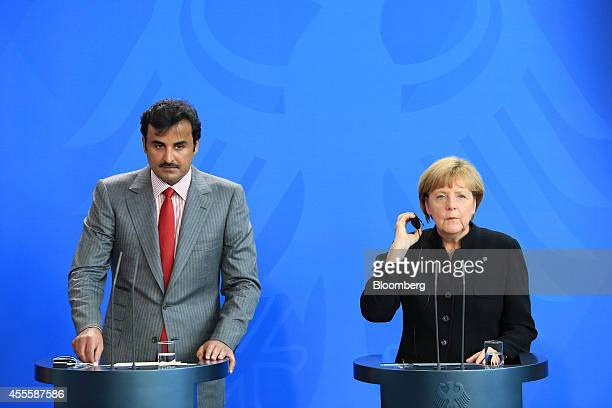 Sheikh Tamim bin Hamad Al Thani the Emir of Qatar left and Angela Merkel Germany's chancellor listen to a journalist's question during a news...