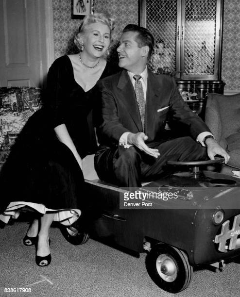 Sheilah Graham columnist whose notes on Hollywood often appear in The Denver Post gets chummy with Bob Cummings in a pintsized automobile he bought...