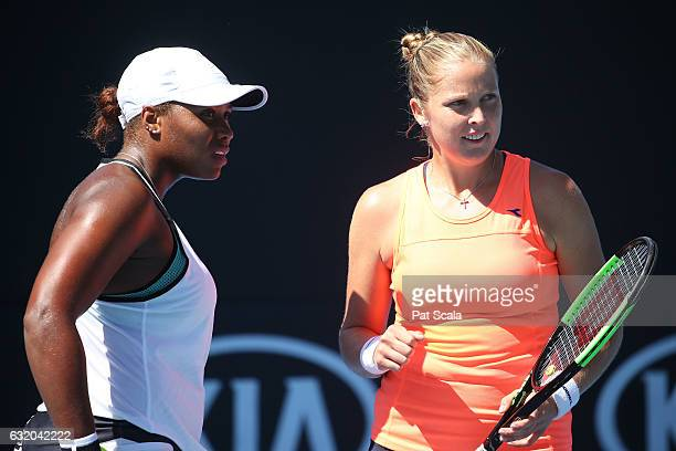 Shelby Rogers and Taylor Townsend of the United States talk tactics in their first round doubles match against Kiki Bertens of the Netherlands and...