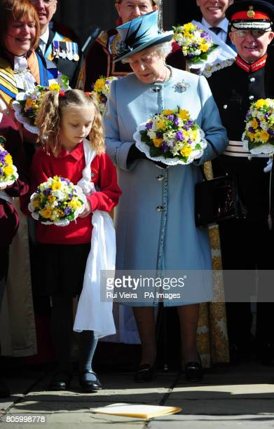 Shelby Rotherham aged 9 and Queen Elizabeth II look at order of service after it was dropped following the Royal Maundy Service outside Derby...