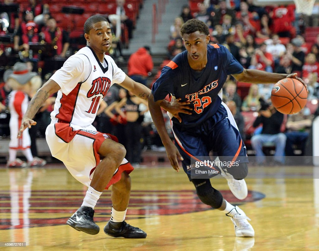 Sheldon Blackwell #22 of the California State Fullerton Titans drives against Daquan Cook #10 of the UNLV Rebels during their game at the Thomas & Mack Center on December 28, 2013 in Las Vegas, Nevada. UNLV won 83-64.