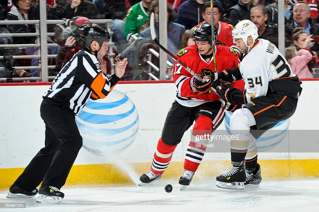 <a gi-track='captionPersonalityLinkClicked' href=/galleries/search?phrase=Sheldon+Brookbank&family=editorial&specificpeople=586095 ng-click='$event.stopPropagation()'>Sheldon Brookbank</a> #17 of the Chicago Blackhawks and <a gi-track='captionPersonalityLinkClicked' href=/galleries/search?phrase=Daniel+Winnik&family=editorial&specificpeople=2529214 ng-click='$event.stopPropagation()'>Daniel Winnik</a> #34 of the Anaheim Ducks battle for the puck as referee Paul Devorski #10 braces for impact during the NHL game on March 29, 2013 at the United Center in Chicago, Illinois.