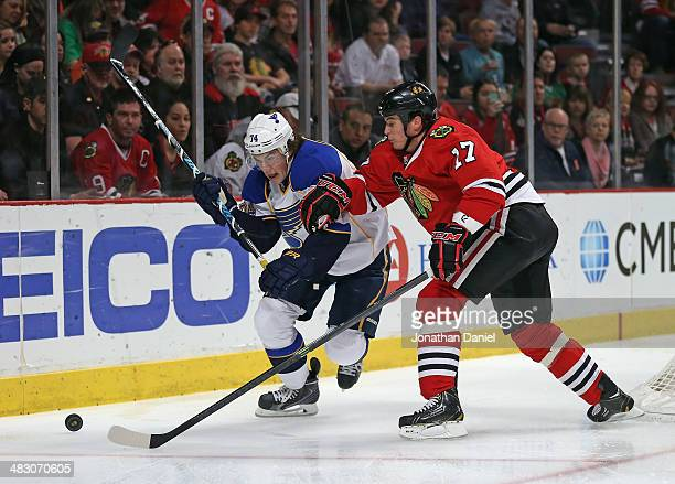 Sheldon Brookbank of the Chicago Blackhawks and TJ Oshie of the St Louis Blues move to the puck at the United Center on April 6 2014 in Chicago...