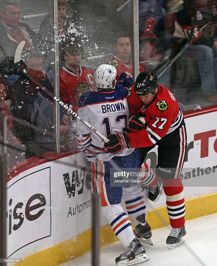 <a gi-track='captionPersonalityLinkClicked' href=/galleries/search?phrase=Sheldon+Brookbank&family=editorial&specificpeople=586095 ng-click='$event.stopPropagation()'>Sheldon Brookbank</a> #17 of the Chicago Blackhawks checks <a gi-track='captionPersonalityLinkClicked' href=/galleries/search?phrase=Mike+Brown+-+American+Ice+Hockey+Right+Winger&family=editorial&specificpeople=7275813 ng-click='$event.stopPropagation()'>Mike Brown</a> #13 of the Edmonton Oilers at the United Center on March 10, 2013 in Chicago, Illinois.