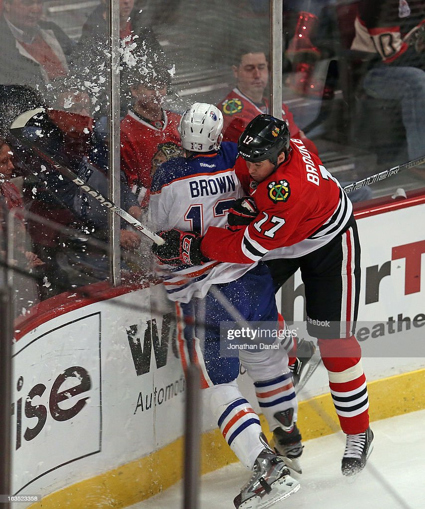 <a gi-track='captionPersonalityLinkClicked' href=/galleries/search?phrase=Sheldon+Brookbank&family=editorial&specificpeople=586095 ng-click='$event.stopPropagation()'>Sheldon Brookbank</a> #17 of the Chicago Blackhawks checks <a gi-track='captionPersonalityLinkClicked' href=/galleries/search?phrase=Mike+Brown+-+American+Ice+Hockey+Right+Winger&family=editorial&specificpeople=7275813 ng-click='$event.stopPropagation()'>Mike Brown</a> #13 of the Edmonton Oilers at the United Center on March 10, 2013 in Chicago, Illinois. The Oilers defeated the Blackhawks 6-5.