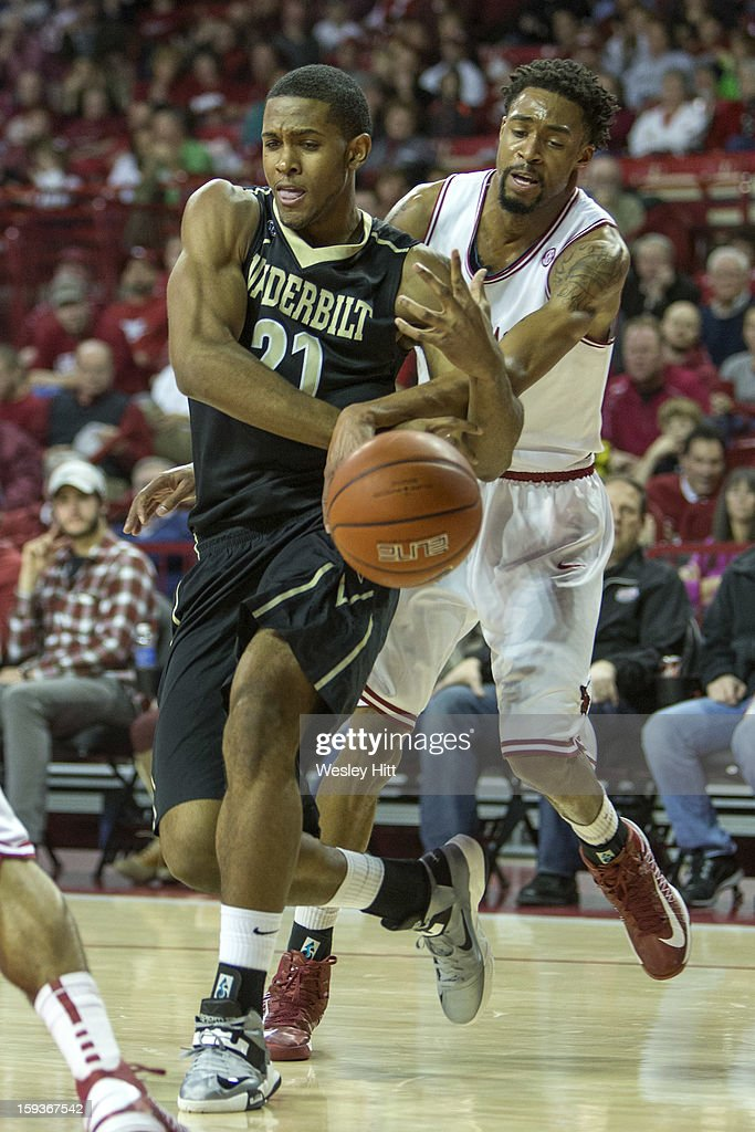 Sheldon Jeter #21 of the Vanderbilt Commodores is fouled from behind by Rashad Madden #00 of the Arkansas Razorbacks at Bud Walton Arena on January12, 2013 in Fayetteville, Arkansas. The Razorbacks defeated the Commodores 56-33.