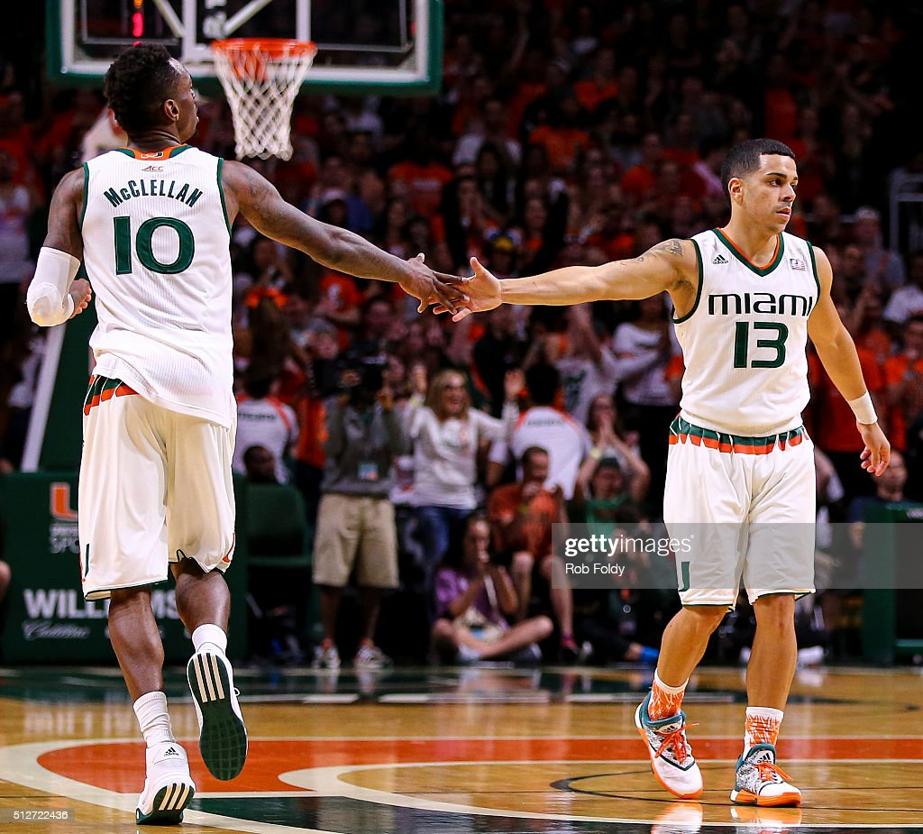 Sheldon McClellan slaps hands with Angel Rodriguez of the Miami Hurricanes during the game against the Louisville Cardinals at the BankUnited Center...