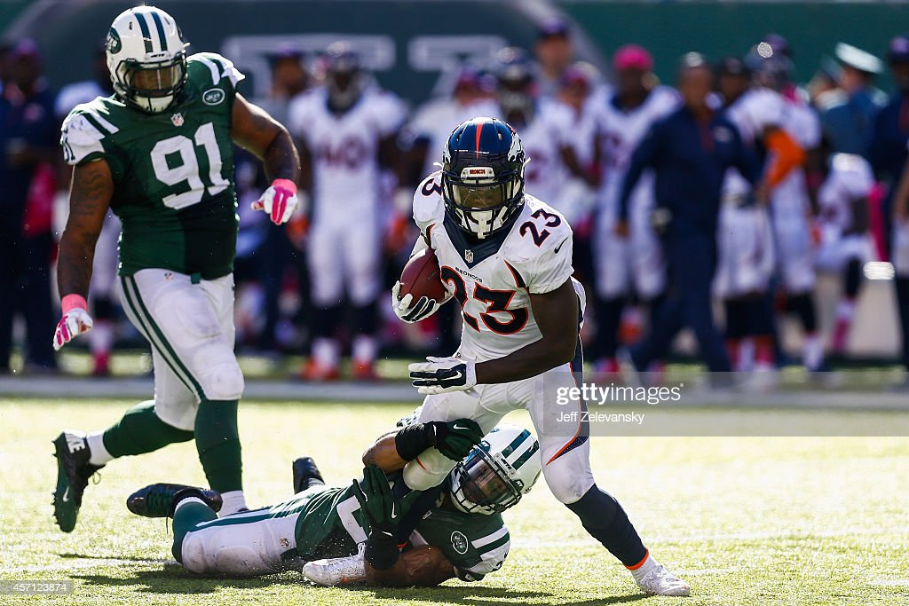 Sheldon Richardson and Dawan Landry of the New York Jets attempt to tackle Ronnie Hillman of the Denver Broncos in the third quarter at MetLife...