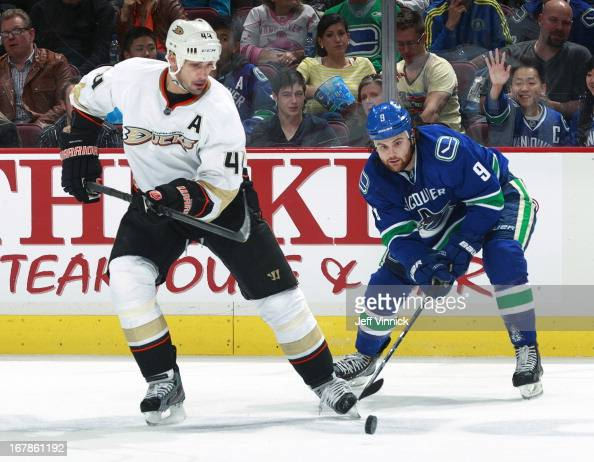 Sheldon Souray of the Anaheim Ducks and Zack Kassian of the Vancouver Canucks watch a loose puck during their NHL game against the Vancouver Canucks...