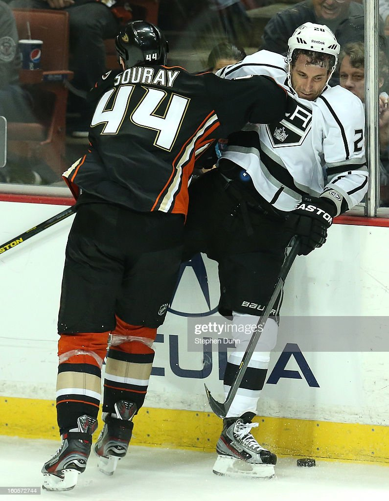 Sheldon Souray #44 of the Anaheim Ducks checks Jarret Stoll #28 of the Los Angeles Kings into the boards at Honda Center on February 2, 2013 in Anaheim, California. The Ducks won 7-4.