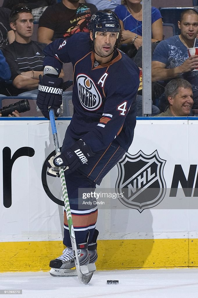 Sheldon Souray of the Edmonton Oilers carries the puck along the boards during a preseason game against the Calgary Flames at Rexall Place on...
