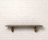 A front view of a regular cleared wooden shelf with wooden brackets on an white brick wall with copy space