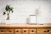 wooden shelf with frame and flower against a brick wall