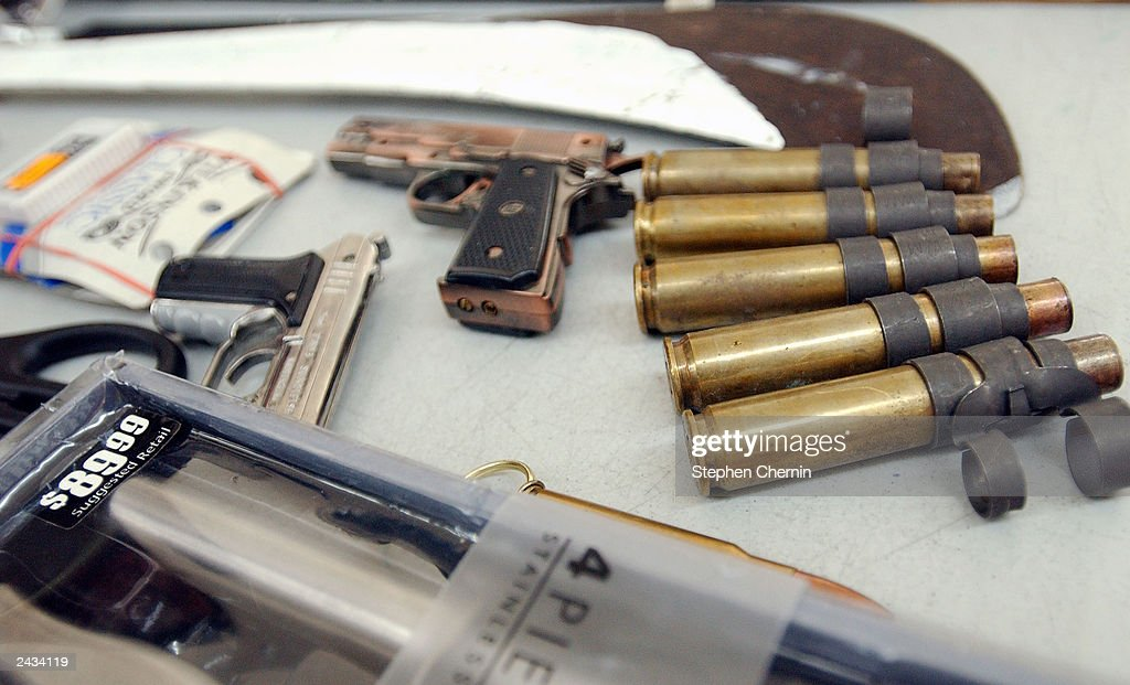 Shell casings fake revolvers a machete and a cutlery set are displayed during a press conference at John F Kennedy airport August 27 2003 in New York...