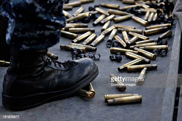 Shell casings from a .50 caliber machine gun around the feet of a soldier.