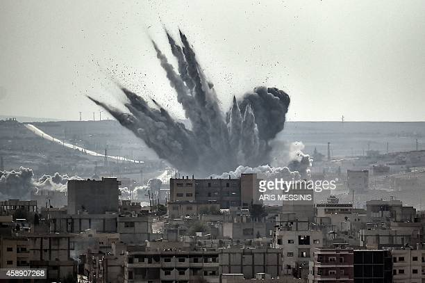 A shell explodes on November 13 2014 in the Syrian city of Kobane also known as Ain alArab as seen from the Turkish border village of Mursitpinar...