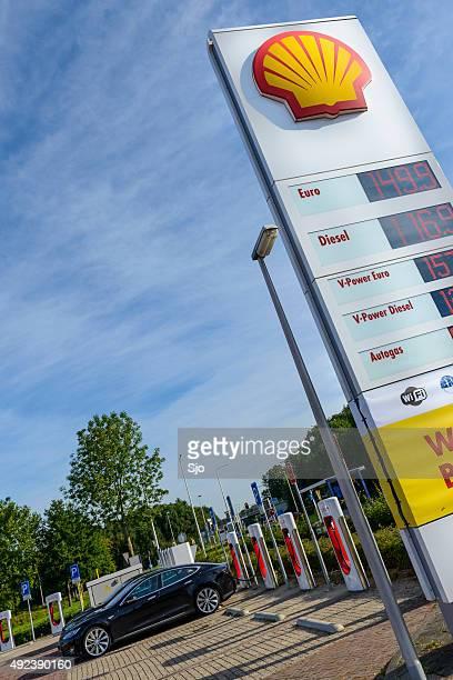 La station essence Shell à côté d'une station de recharge pour voiture électrique Tesla supercharger