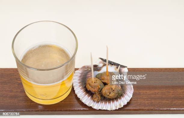 shell of  small scallops in vieira sauce and glass of beer