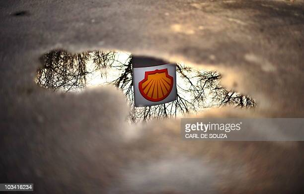 A Shell petrol station logo is refelected in a puddle in London on Februrary 4 2010 Royal Dutch Shell plans to axe 1000 more jobs and sell some of...
