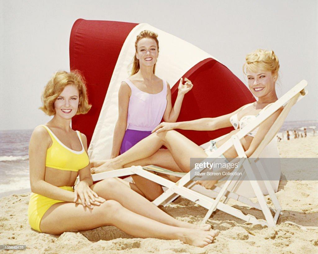 Shelley Fabares US actress and singer wearing a yellow bikini alongside two women in beachwear posing on a beach circa 1965