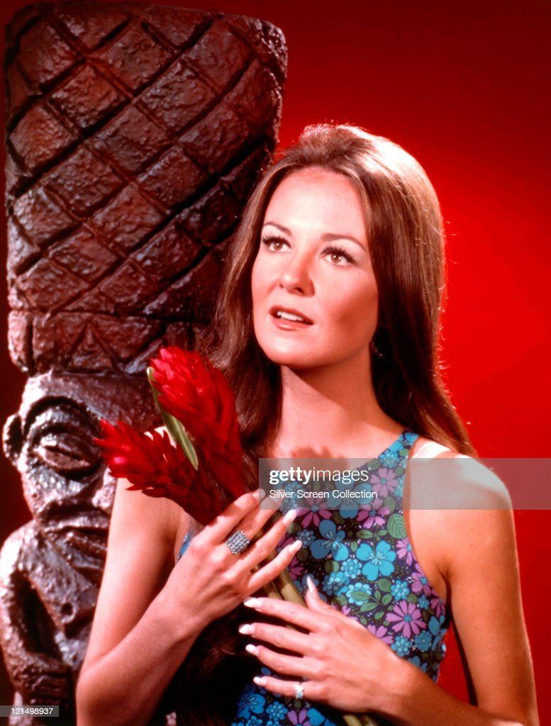 Shelley Fabares US actress wearing a floral print sleeveless dress holding a red flowers posing beside a Polynesian sculpture in a studio portrait...