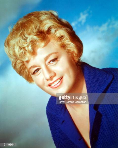 Shelley Winters US actress smiling and wearing a dark blue blouse in a studio portrait against a background of blue sky and clouds circa 1965