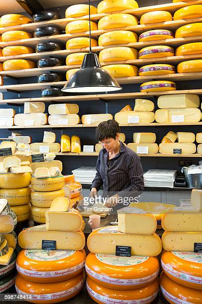 Shelves of cheese wheels and woman cutting cheese wedge at cheese shop 't Kaaswinkeltje in Gouda The Netherlands