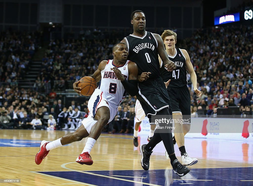 Shelvin Mack of Atlanta Hawks goes past Andray Blatche of Brooklyn Nets during the Eastern Conference NBA match between Brooklyn Nets and Atlanta Hawks at O2 Arena on January 16, 2014 in London, England.