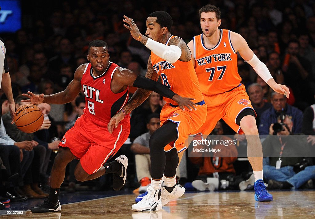 Shelvin Mack #8 of the Atlanta Hawks drives around J.R. Smith #8 and Andrea Bargnani #77 of the New York Knicks at Madison Square Garden on November 16, 2013 in New York City. The Hawks defeat the Knicks 110-90.