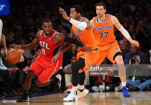 Shelvin Mack of the Atlanta Hawks drives around JR Smith and Andrea Bargnani of the New York Knicks at Madison Square Garden on November 16 2013 in...